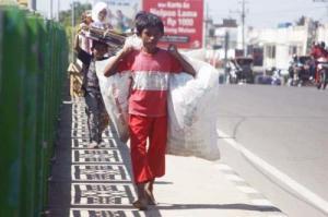 Seorang anak menyusuri trotoar yang panas, demi seonggok botol plastik yang mungkin ia temukan. Potret buram sebagian anak Indonesia. Generasi yang hilang ?