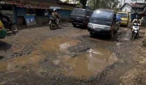 Terlihat air sisa banjir di sebuah jalan raya. Menurut warga, jalan tsb sudah sering mencelakakan pengendara motor.