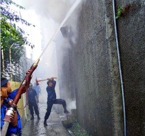 Petugas diskar sedang memadamkan api dari gang yang sempit.